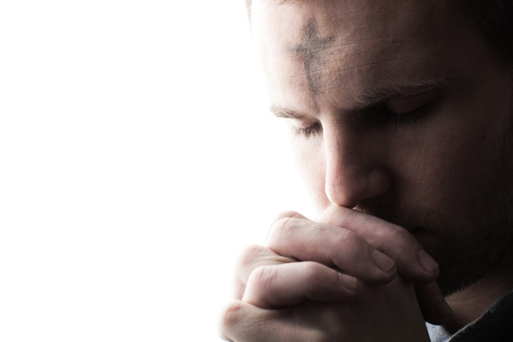 Photo of a man praying with ashes on his forehead