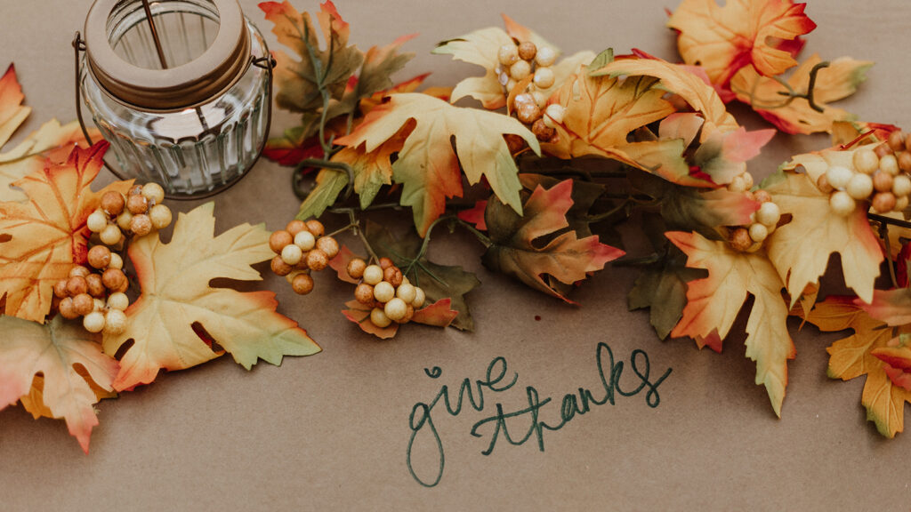 Thanksgiving image of fall leaves and a candle with the text 'give thanks.'